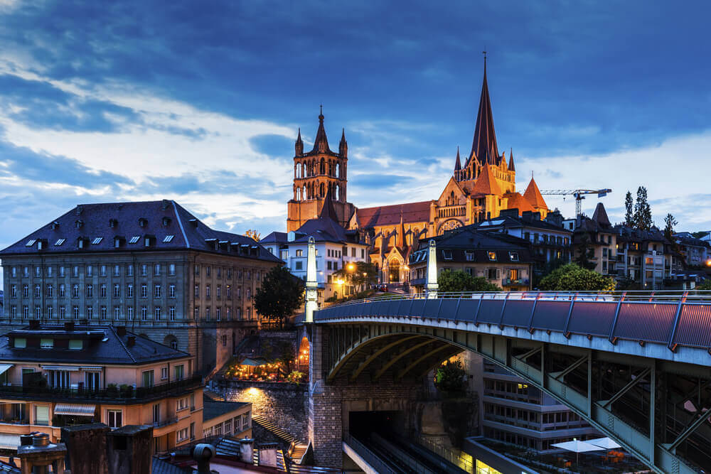 city of lausanne with a cathedral at dusk