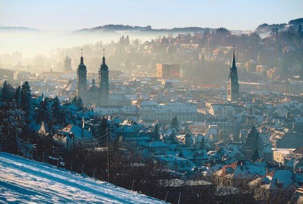 St.Gallen Stadt bei Sonnenaufgang mit Häusern und drei Kirchentürmen.